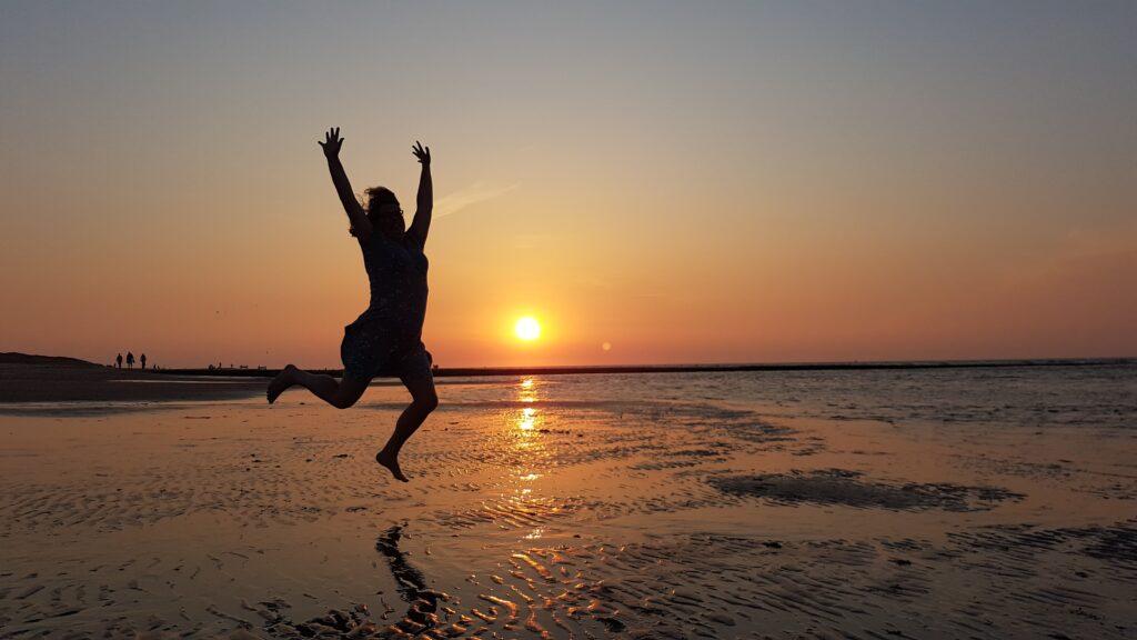 springende Floortje Janssen, healer, reader, coach bij ondergaande zon op het strand